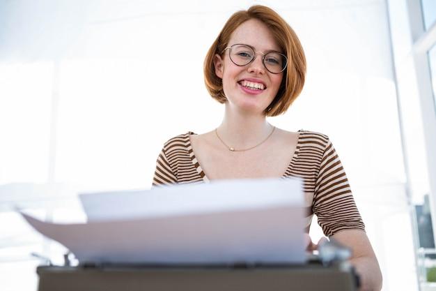 Donna sorridente hipster seduto a una scrivania, digitando sulla sua macchina da scrivere