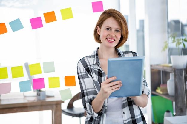 Donna sorridente hipster, seduto alla sua scrivania sul suo tablet