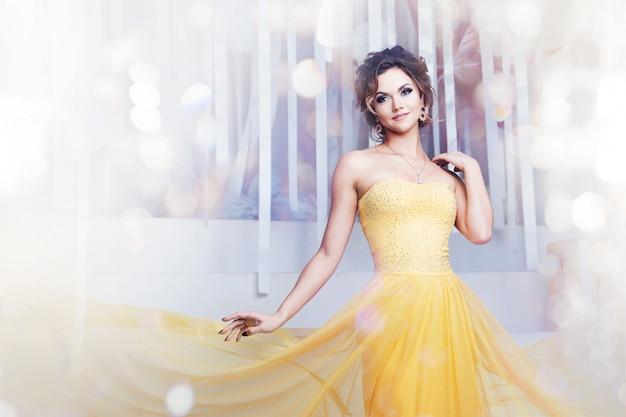 Donna sorridente in abito da sera giallo e con bella acconciatura, festa