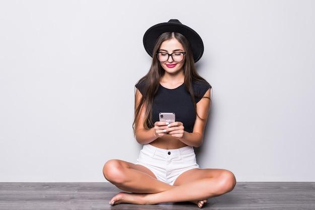 Donna sorridente in black hat che si siede sul pavimento e che per mezzo dello smartphone isolato sopra fondo grigio