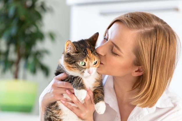 Donna sorridente in camicia bianca che bacia e che abbraccia con tenerezza e amore gatto, tenendola tra le braccia