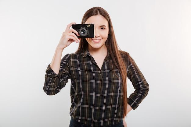 Donna sorridente in camicia che fa foto sulla retro macchina fotografica