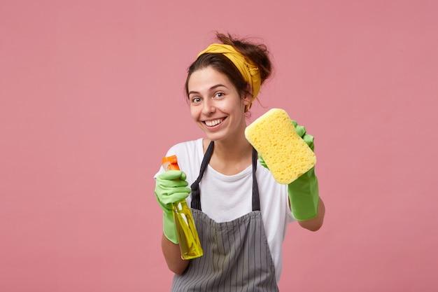 Donna sorridente in grembiule e guanti di gomma che mostrano spugna ordinata e detersivo isolato