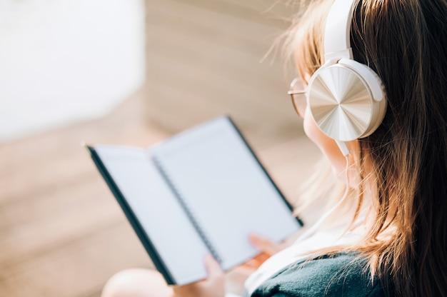 Donna sorridente in libro di lettura degli occhiali e ascoltare la musica con le cuffie in parco all'aperto contro luce solare, concetto di stile di vita della città.
