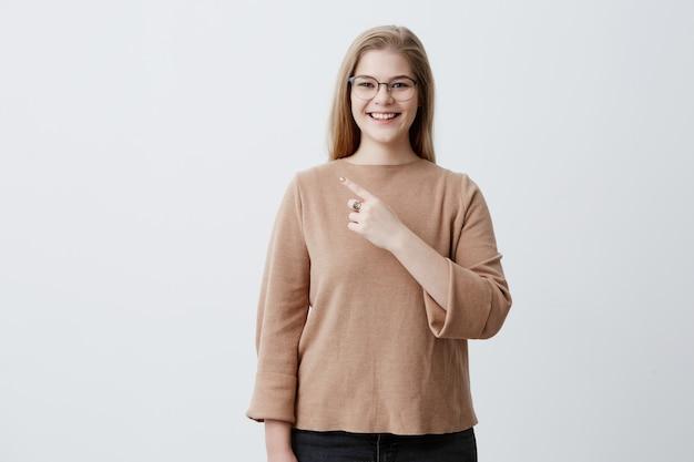 Donna sorridente in maglione e occhiali alla moda con i capelli biondi dritti che punta al muro bianco bianco, dimostrando qualcosa. femmina allegra che indica con il dito anteriore su fondo grigio.
