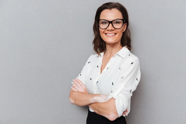 Donna sorridente in occhiali e abiti d'affari in posa con le braccia incrociate e guardando la telecamera su grigio