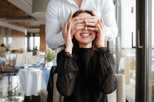 Donna sorridente in ristorante con l'uomo dietro di lei
