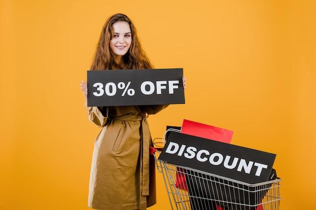 Donna sorridente in trench con il segno di sconto del 30% e sacchetti della spesa variopinti in carrello isolato sopra giallo