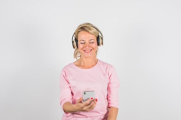 Donna sorridente invecchiata in camicetta rosa con le cuffie tramite smartphone