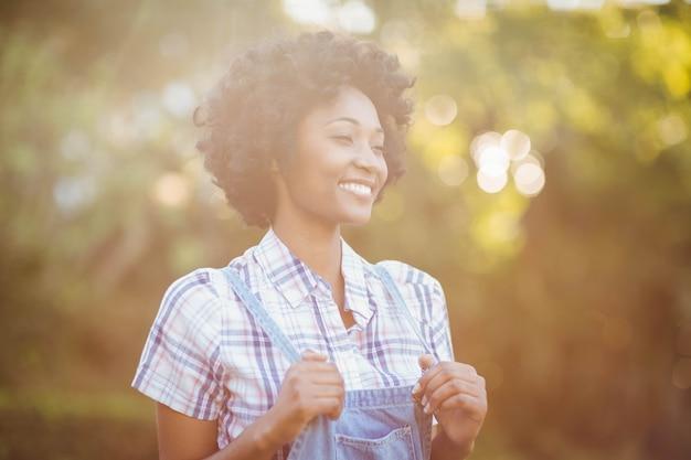 Donna sorridente nel giardino che osserva via