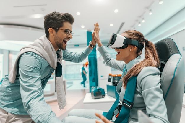 Donna sorridente nell'usura convenzionale che prova la tecnologia di realtà virtuale mentre sedendosi nella sedia nel deposito di tecnologia