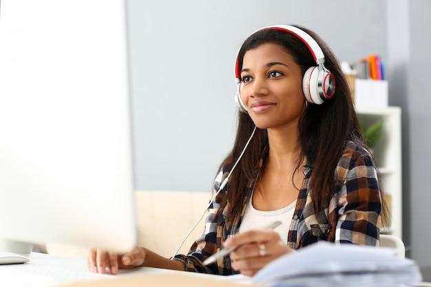 Donna sorridente nera che si siede nel luogo di lavoro indossando le cuffie