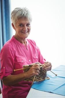 Donna sorridente pensionata che fa un certo lavoro a maglia