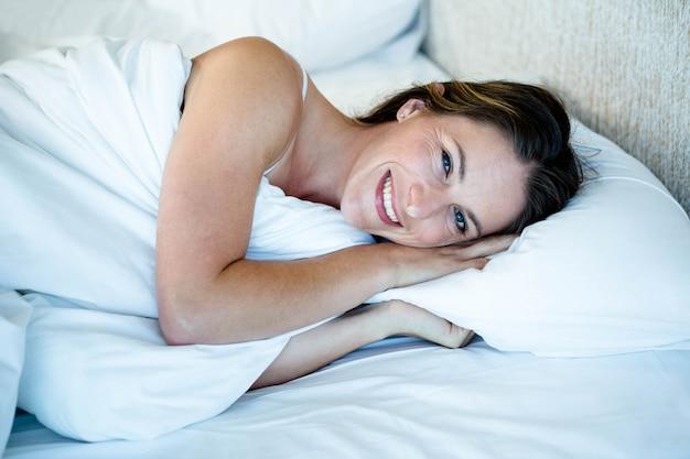 Donna sorridente sdraiata nel suo letto con il piumone su di lei