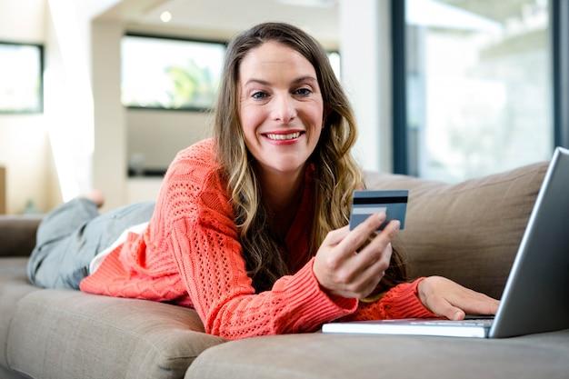 Donna sorridente sdraiata sul divano con il suo computer portatile e la carta di credito
