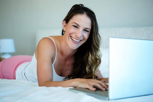 Donna sorridente sdraiata sul suo letto, digitando sul suo computer portatile