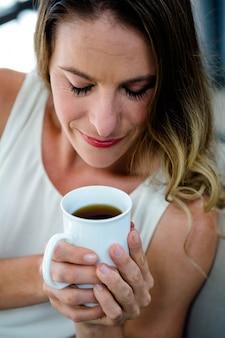 Donna sorridente seduta su un divano, sorseggiando una tazza di caffè