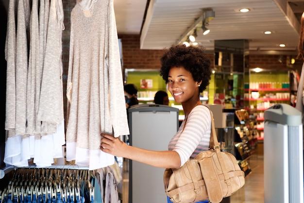 Donna sorridente shopping nel negozio di abbigliamento