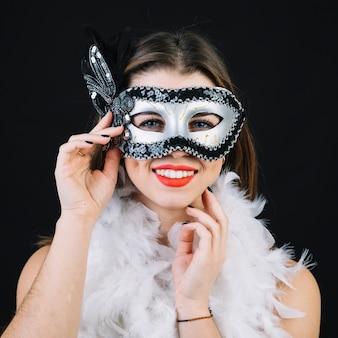 Donna sorridente splendida con la piuma bianca del boa su priorità bassa nera