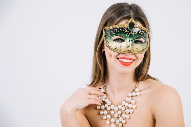 Donna sorridente splendida nella maschera e nella collana di carnevale di travestimento su fondo bianco
