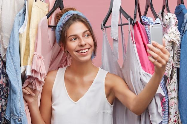 Donna sorridente sveglia che prende autoritratto sul telefono cellulare generico, che posa nel suo guardaroba, vantandosi delle nuove cime e dei vestiti alla moda che ha comprato nella vendita questa mattina