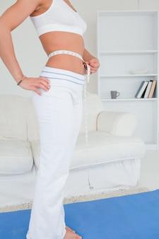 Donna sottile che misura la sua pancia