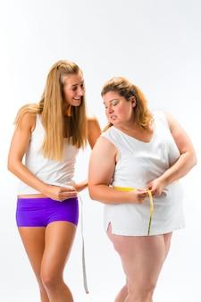 Donna sottile e grassa che misura vita con nastro adesivo