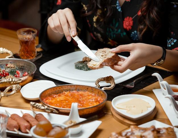 Donna spalmando il burro sul pane nella tradizionale colazione