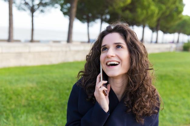Donna spensierata allegra che gode della conversazione piacevole del telefono