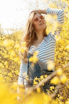 Donna spensierata con gli occhiali da sole che posano nel giacimento di fiore