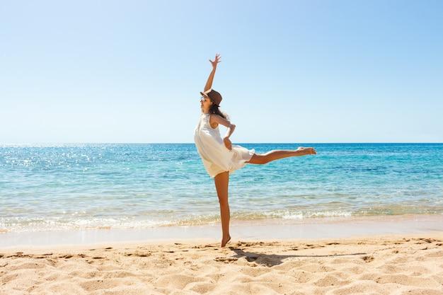 Donna spensierata felice ballando in spiaggia. concetto di stile di vita felice libertà