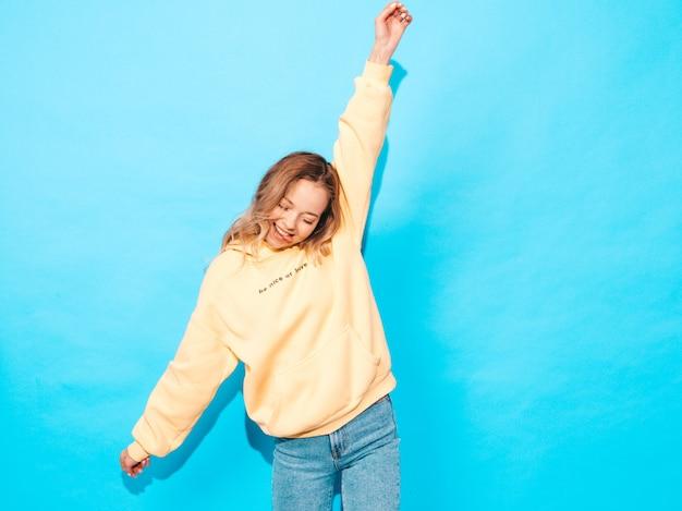 Donna spensierata sexy che posa vicino alla parete blu. divertimento del modello positivo alzando le mani e mostrando la lingua