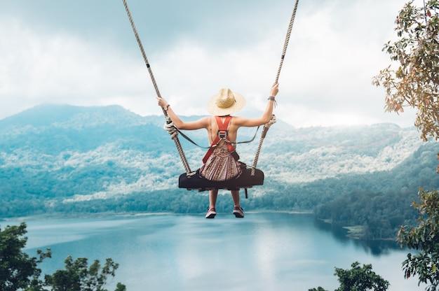 Donna spensierata sull'altalena su un paesaggio stimolante. concetto di sogno