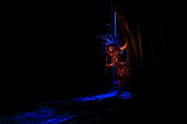 Donna spettrale, spirito del teatro. un attore che guarda fuori da dietro le quinte