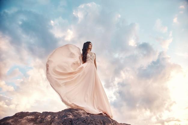 Donna splendida castana nelle montagne al tramonto e cielo blu con le nuvole