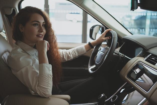 Donna splendida che compra nuova automobile al concessionario