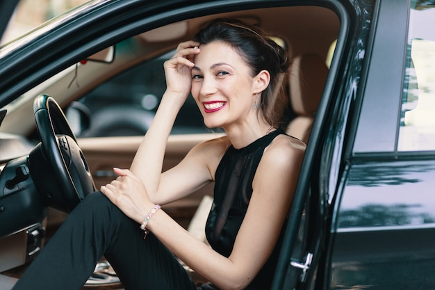 Donna splendida che ride, felice mentre era seduto sul sedile anteriore