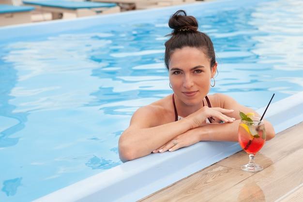 Donna splendida che si rilassa alla piscina