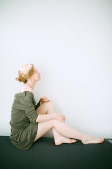 Donna splendida che si siede e che pensa con i suoi occhi chiusi nella sala con fondo bianco in vestito verde.