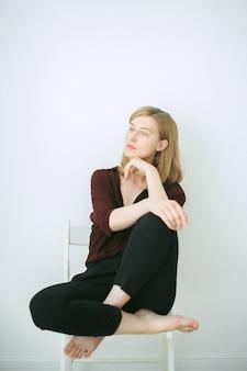 Donna splendida che si siede su una sedia e che pensa nella sala con il fondo bianco in camicia marrone e pantaloni neri.