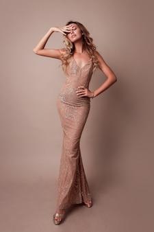 Donna splendida con capelli ondulati biondi che indossa elegante abito beige