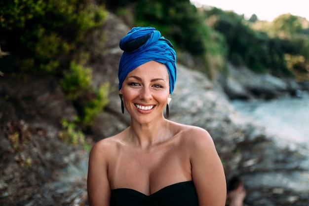 Donna splendida con il foulard e sorriso che guarda l'obbiettivo all'aperto. avvicinamento.