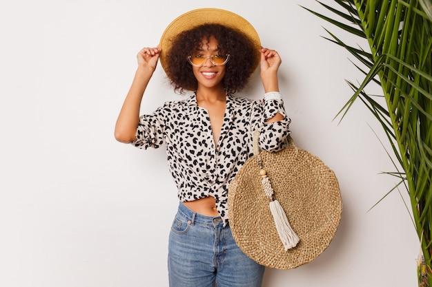Donna splendida con pelle scura in jeans e cappello di paglia che posano nello studio sopra fondo bianco con la borsa nello stile di bali. umore frenetico.
