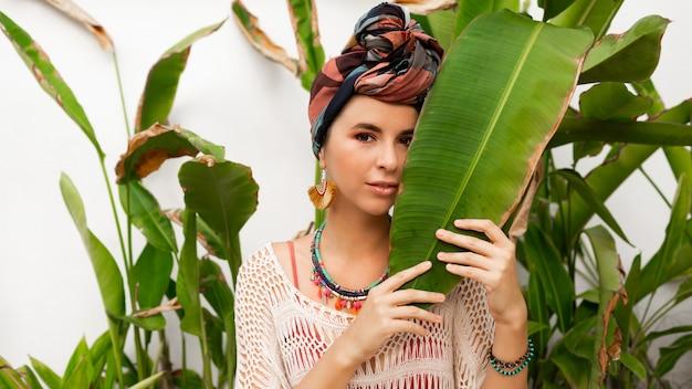 Donna splendida con turbante sulla testa, orecchini colorati e posa della collana di boho