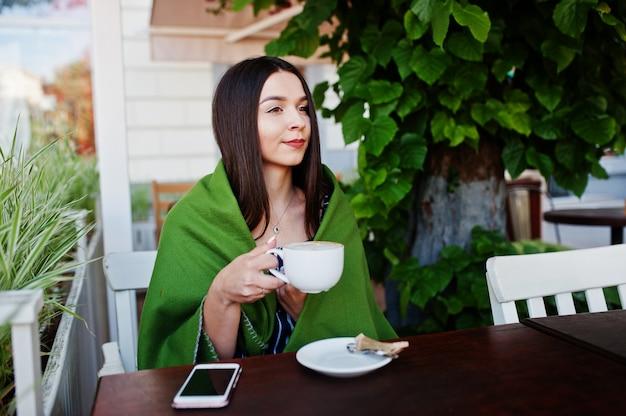 Donna splendida del brunette che si siede sulla tabella in plaid della copertura del caffè con la tazza di caffè.