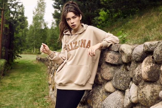 Donna splendida del brunette in maglia con cappuccio di modo nel vicolo del giardino