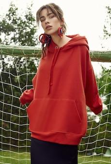 Donna splendida del brunette in maglia con cappuccio rossa di modo sul campo sportivo