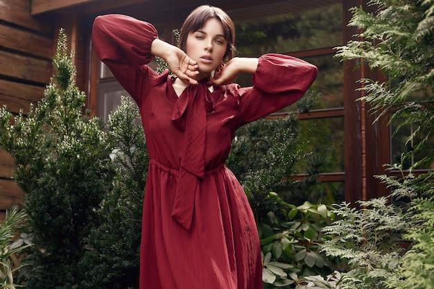 Donna splendida del brunette in vestito rosso da modo in giardino