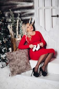 Donna splendida di pregancy in calzini rossi della tenuta sullo stomaco. natale.