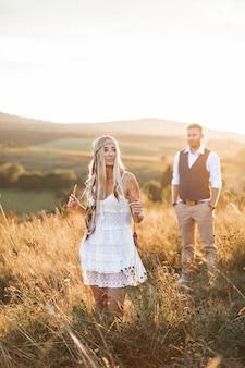 Donna splendida felice in abiti stile boho e uomo elegante che cammina nel campo estivo